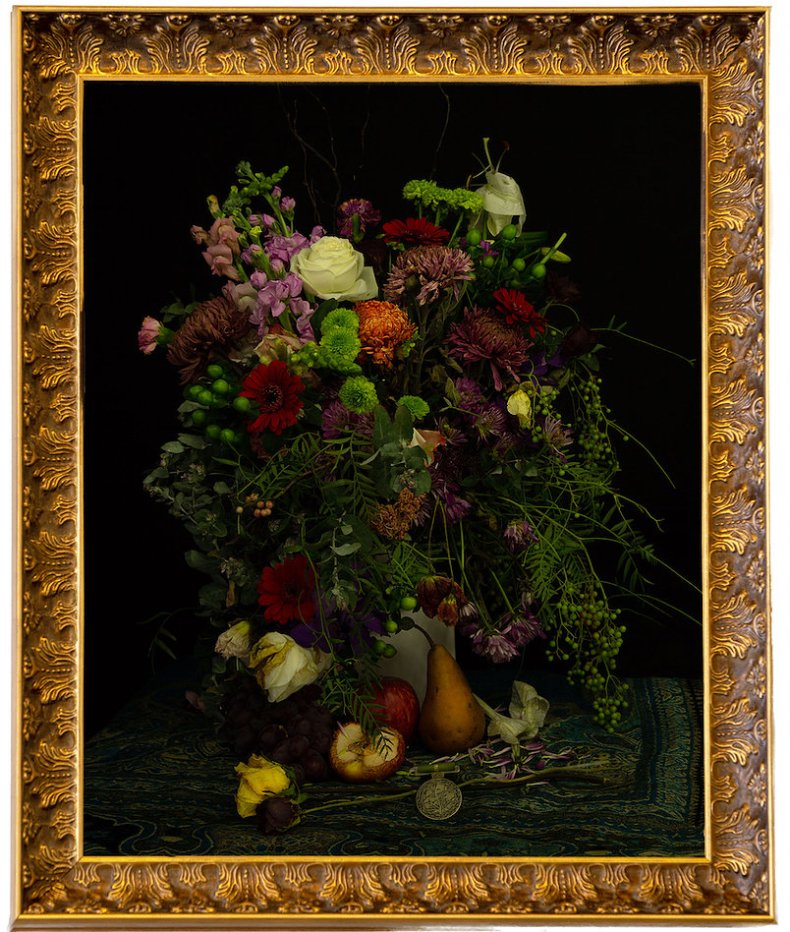A lush bunch of flowers on a dark table with a dark background.