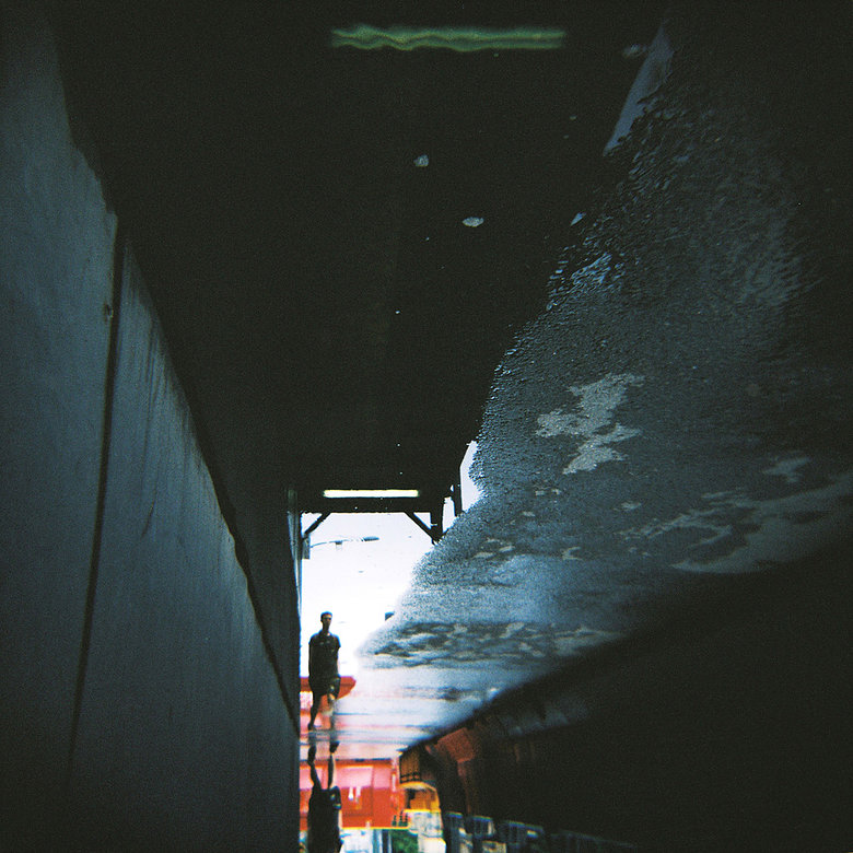Upside down photo of a wet street. There is a small sillhouetee of a someone at the bottom.