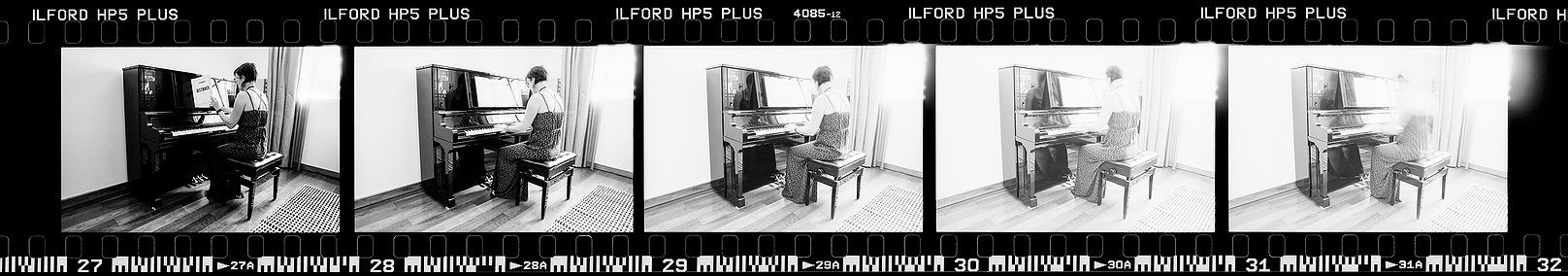 Negative strip of five frames progressively getting overexposed, that show someone at piano.